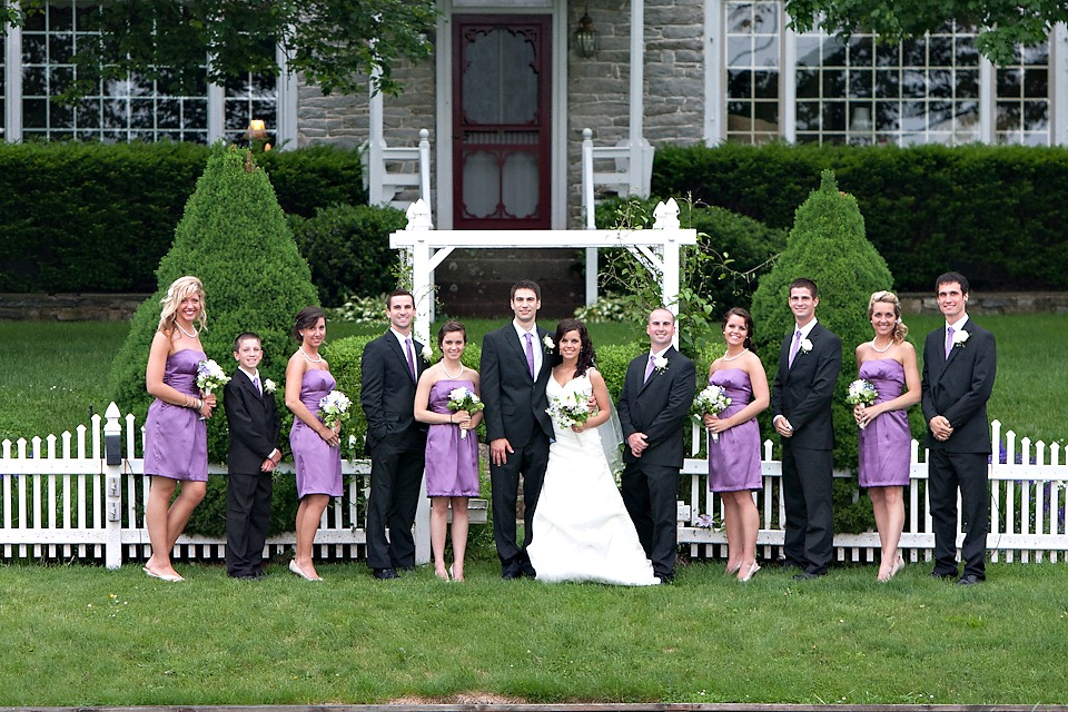 Wedding party posing in front of Lancaster County Farm