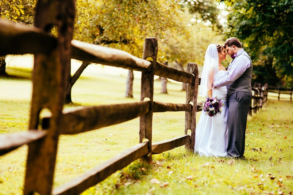 Bride and Groom leaning on the fence at historic Ephrata Cloister